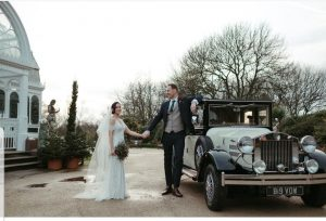 vintage wedding car outside the palm house sefton park with the tallest groom barringtons have ever had