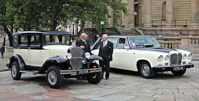 wedding car drivers chatting outside the st georges hall liverpool next to vintage wedding car